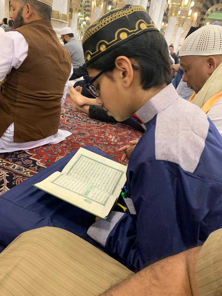 Big kids learn about Hajj by reading Quran.